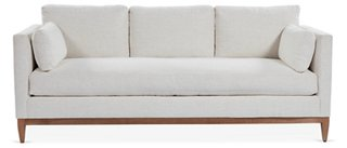 With its tailored silhouette and neutral-hued upholstery, this versatile sofa works well in just about any style of decor - Leo Sofa at OKL. #sofas #furniture #whitesofa #woodplatform #singlecushion #whitedecor #livingroom